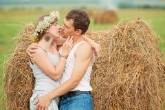 Le coppie romantiche si avvicinano al mucchio di fieno Fotografia Stock