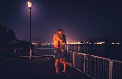 Le coppie romantiche stanno baciando nell'argine del lago alla notte e nelle luci della città sui precedenti Coppia sposata di Fotografia Stock Libera da Diritti