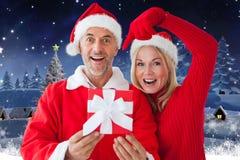 Le coppie in Santa costume la mostra del loro regalo contro il fondo digitalmente generato di natale fotografia stock libera da diritti