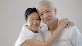 Le coppie senior asiatiche felici su fondo bianco amano ed abbracciano Fotografie Stock Libere da Diritti
