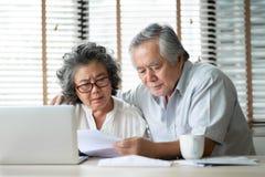 Le coppie senior calcolano la loro spesa mensile immagini stock