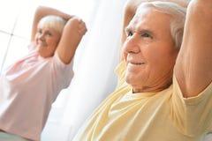 Le coppie senior esercitano insieme a casa l'allungamento della spalla di sanità Immagini Stock