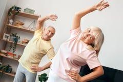 Le coppie senior esercitano insieme a casa l'allungamento relativo alla ginnastica di sanità Fotografie Stock Libere da Diritti
