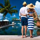 Le coppie si avvicinano al poolside fotografia stock