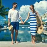 Le coppie si avvicinano al poolside fotografia stock libera da diritti