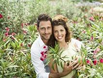 Le coppie si divertono scegliendo i vasi da fiori in una serra Fotografie Stock Libere da Diritti