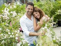 Le coppie si divertono scegliendo il fiore in una serra Fotografie Stock Libere da Diritti