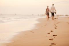 Le coppie si rilassano insieme sulla spiaggia Fotografie Stock