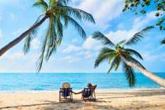 Le coppie si rilassano sulla spiaggia che gode di bello mare sull'isola tropicale fotografia stock