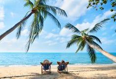 Le coppie si rilassano sulla spiaggia che gode di bello mare sull'isola tropicale fotografia stock libera da diritti