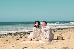Le coppie si siedono sulla spiaggia Immagini Stock