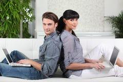 Le coppie si sono sedute con un computer portatile Immagine Stock Libera da Diritti