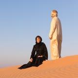 Le coppie si sono vestite in abbigliamento arabo tradizionale in deserto Immagini Stock