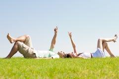 Le coppie si trovano giù su erba Fotografia Stock