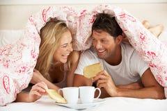 Le coppie Snuggled sotto il Duvet che mangia la prima colazione Fotografia Stock