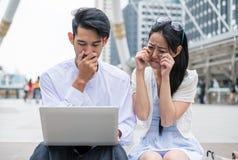 Le coppie sono si siedono per mezzo del computer portatile con triste circa l'incidente qualcosa i immagini stock libere da diritti