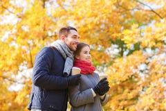 Le coppie sorridenti con le tazze di caffè in autunno parcheggiano Fotografia Stock