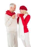 Le coppie sorridenti nell'inverno adattano la tostatura con le tazze Fotografia Stock