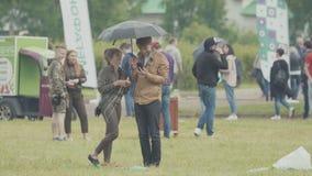 Le coppie sotto l'ombrello su prato inglese alla città hanno ammucchiato il festival dell'estate del parco stock footage