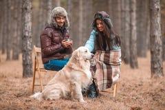 Le coppie stanno sedendo su una sedia vicino con il documentalista nella foresta di autunno Immagini Stock