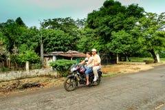 Le coppie su un motore bike su una strada non asfaltata Fotografie Stock Libere da Diritti
