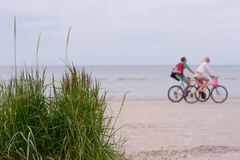 Le coppie su una bici guidano lungo la spiaggia Fotografia Stock Libera da Diritti