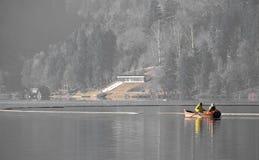 Le coppie sull'imbarcazione a remi di rilassamento di viaggio sul lago hanno sanguinato nell'inverno Immagine Stock Libera da Diritti