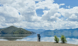 Le coppie tengono insieme distogliere lo sguardo sulla spiaggia immagini stock