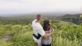 Le coppie turistiche che considerano la montagna e gli altopiani hanno coperto la foresta verde sul fondo dell'orizzonte Abbracci stock footage