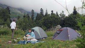 Le coppie turistiche che riposano sulla tenda di campeggio in montagna abbelliscono stock footage