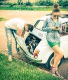 Le coppie in un momento delle difficoltà durante l'automobile classica d'annata scattano Immagini Stock Libere da Diritti