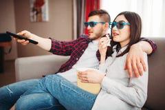 Le coppie in vetri 3D guardano la TV con popcorn Immagini Stock