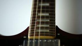 Le corde della chitarra del primo piano strimpellano stock footage
