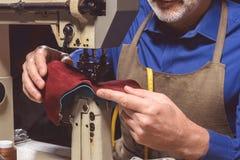 Le cordonnier dans le tablier coud des chaussures Image libre de droits