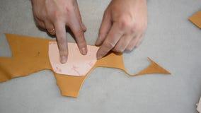 Le cordonnier fait le modèle sur le papier et coupe le cuir clips vidéos