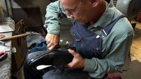 Le cordonnier réparant une chaussure dans l'atelier 4k a coupé les robinets sur les chaussures banque de vidéos