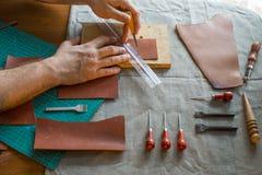 Le cordonnier répare la chaussure Le cordonnier coud des chaussures Atelier de cordonnier Cuir de coupe de cordonnier dans un ate photo libre de droits