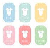 Le corps de bébé adapte à des vêtements sur des cintres Annonces en pastel de bébé et cartes de douche Image stock