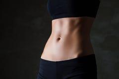 Le corps de la femme mince au-dessus du fond gris-foncé Image stock