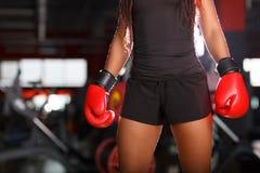 Le corps de la jeune belle femme africaine dans les gants de boxe rouges dans un gymnase Modèle de forme physique Concept de spor images libres de droits