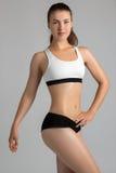 Le corps folâtre une femme attirante sur un fond gris Photos stock