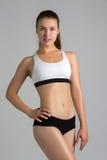 Le corps folâtre une femme attirante sur un fond gris Photographie stock libre de droits