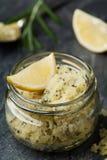 Le corps frottent du sel de mer avec le citron, le romarin et l'huile d'olive dans le pot en verre sur la table en pierre images libres de droits