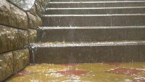 Le correnti di acqua piovono a dirotto i punti delle scale nel parco durante la pioggia di versamento Movimento lento 4K archivi video