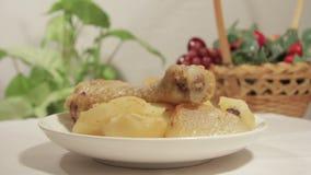 Le coscie di pollo con la patata sono servito sul piatto bianco archivi video