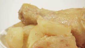 Le coscie di pollo con la patata sono servito sul piatto bianco stock footage