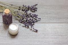 Le cosmétique écrème avec des fleurs de lavande sur la table en bois noire Photographie stock libre de droits