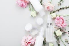 Le cosmétique naturel réglé de la crème, de la lotion et de la crème hydratante a décoré des fleurs et des feuilles de vert sur l Photo stock