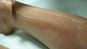 Le Cosmetologist applique le gel aux pieds patients du ` s avant procédure d'epilation clips vidéos