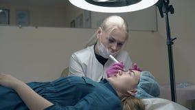 Le Cosmetologist applique le sourcil permanent dans le salon de beaut? banque de vidéos
